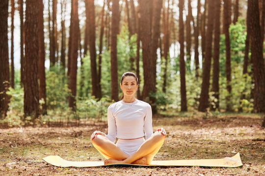 Young beautiful woman with pleasant appearance sitting on karemat in yoga pose and looking directly at camera with calm and relaxed expression, sport training in open air.