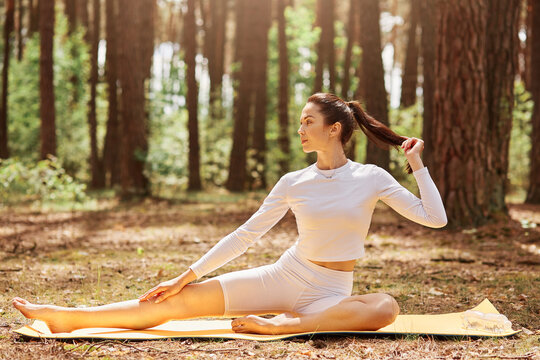 Portrait of young woman sitting on karemat in forest or park and looking away, touching her ponytail, relaxing and practicing yoga, healthy lifestyle.