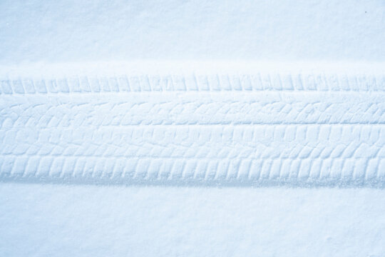 Tire trace in the snow. Winter tires or winter driving background.