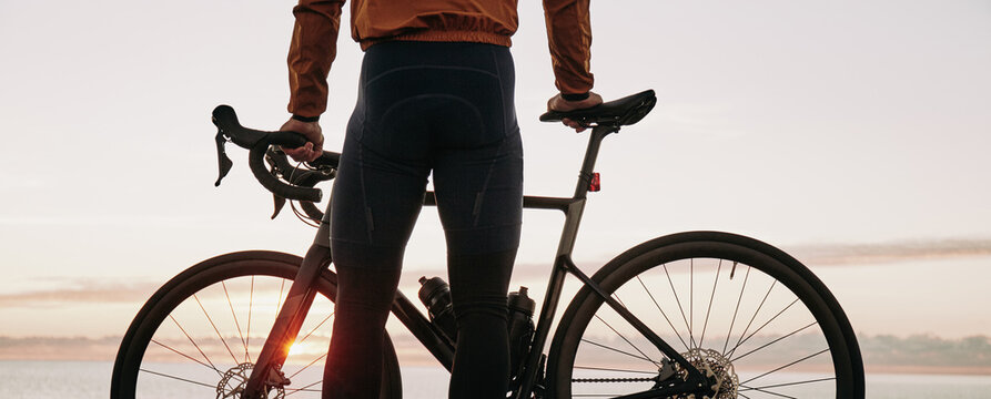 Cyclist watching the sunset over the ocean