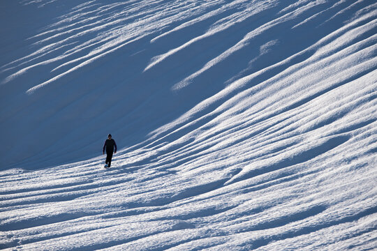 silhouette of person walking in snow