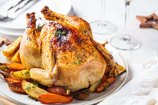 Christmas baked whole chicken stuffed with thyme, lemon and vegetables.