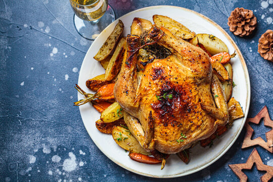 Christmas baked whole chicken stuffed with thyme, lemon and vegetables. Christmas food, holiday dish, decorated background.