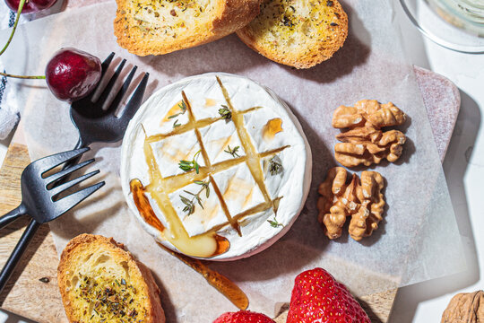 Baked Camembert or Brie with thyme and maple syrup. Cheese, fruits, bread and nut to white wine.