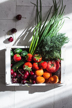 Summer harvest of fruits and vegetables in white wooden box on tile background. Plant-based diet concept.