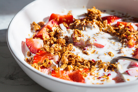 Granola with yogurt and strawberries in white bowl, close-up. Healthy breakfast concept.