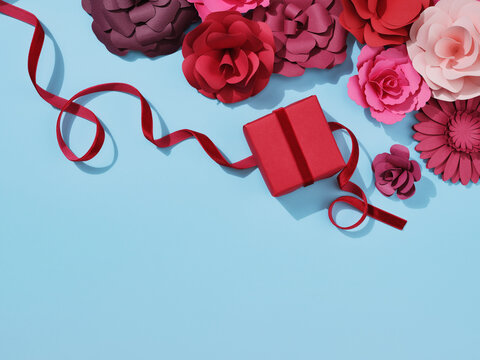 Red and pink paper crafted flowers and roses. and a paper gift with ribbon.