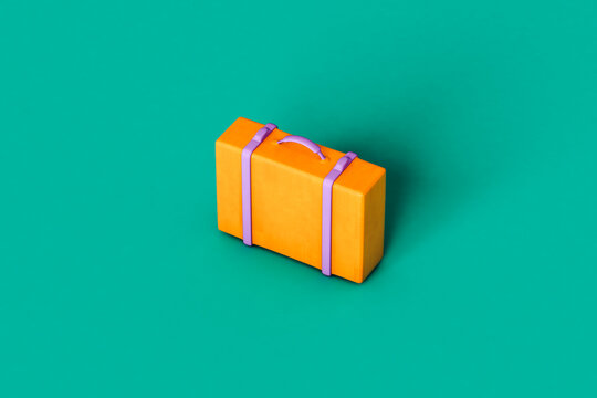 a single orange suitcase on green background