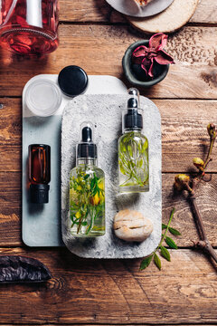 Aromatic oils with herbs in transparent bottles on wooden background
