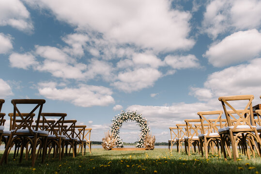 place for wedding ceremony with arch and wooden chairs