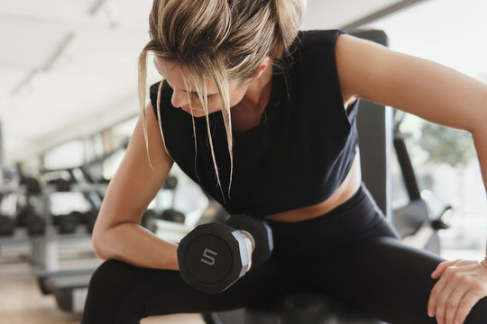 Athletic woman doing bicep curl exercise with a dumbbells in the gym