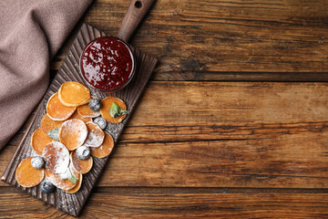 Cereal pancakes with jam and blueberries on wooden table, flat lay. Space for text