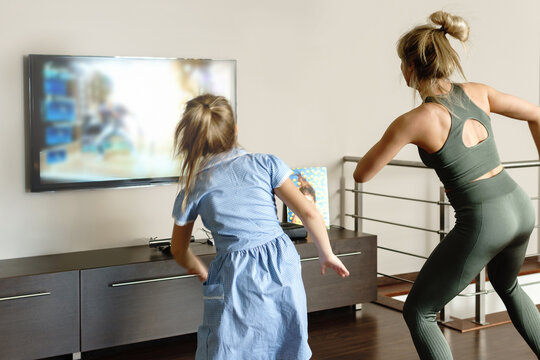 Family dancing with modern video game console at home