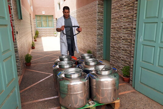 A worker pushes containers of argan oil in Tiout, near Taroudant