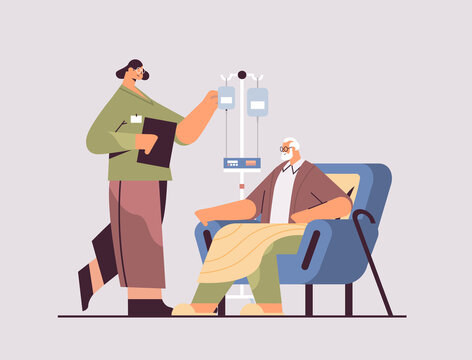 female nurse or volunteer checking dripper of elderly man patient home care services healthcare and social support