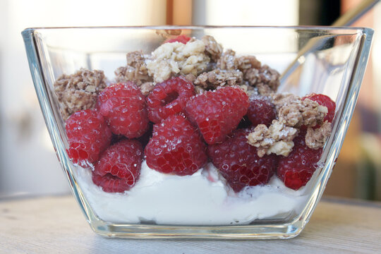 Naturjoghurt mit frischen Himbeeren und Knuspermüsli in Glasschale