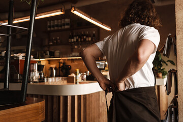 Young white cafe worker in apron standing indoors - fototapety na wymiar