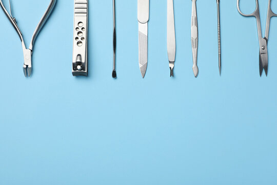Set of manicure tools on light blue background, flat lay. Space for text