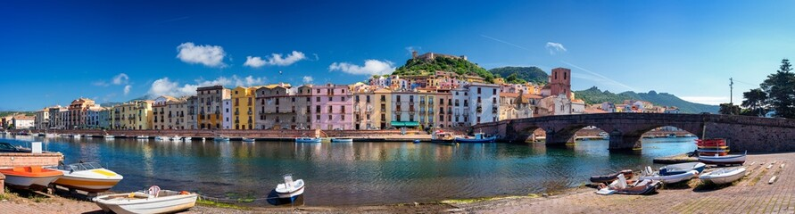 """Panoramic view Bosa riverside with the bridge """" Ponte Vecchio """" and the Malaspina Castle in background. Bosa the colorful town. Stitched panorama."""