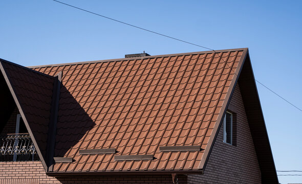 Brown corrugated metal profile roof installed on a modern house. The roof of corrugated sheet. Roofing of metal profile wavy shape. Modern roof made of metal. Metal roofing.
