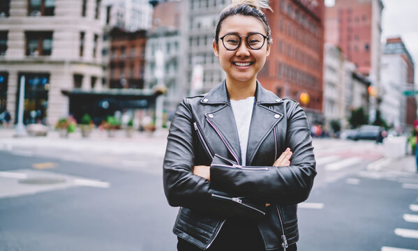 Half length portrait of cheerful female tourist in optical eyewear and terndy leather jacket posing at urban street, happy Japanese hipster girl with crossed hands smiling at camera during vacations