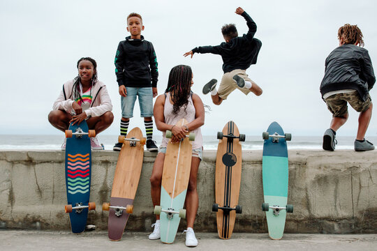 Family with skateboards jumping from seawall