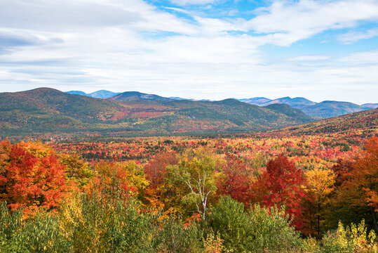 Majestc wooded mountain landscape during the autumn colour season on a partly cloudy day. White Mountains, NH, USA.
