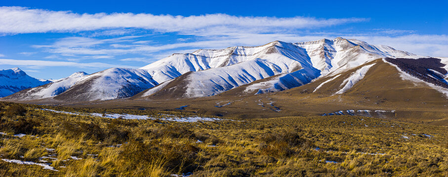 Winter landscape in Patagonia: snow covered hills rising from the pampas