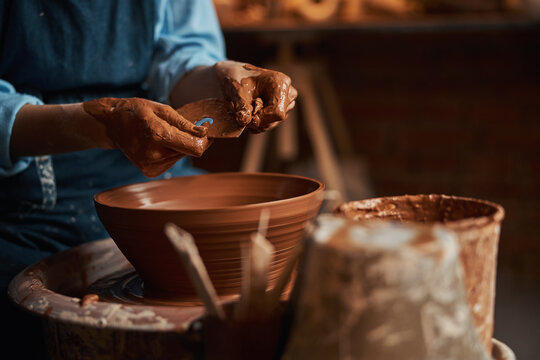 Elegant arms of female artisan in clay while making bowl in pottery workshop