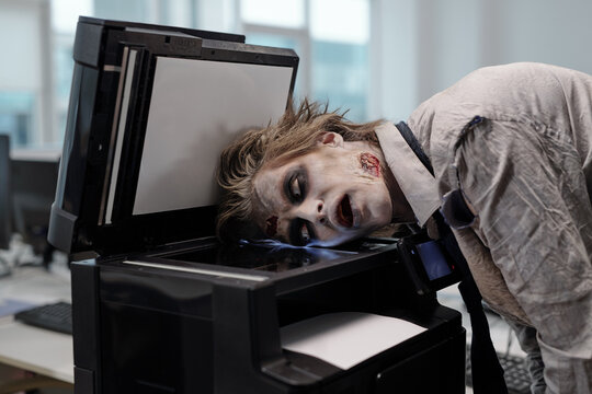 Gloomy man with zombie greesepaint on face keeping head on screen of xerox machine