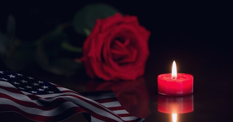 Composition of lit red candle and red rose with american flag on black background