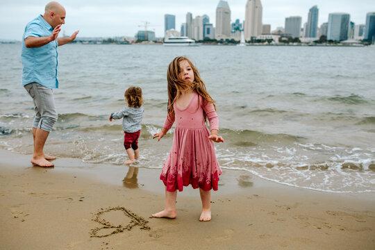 Girl on beach draws heart in the sand