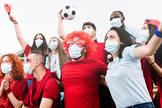 Multiracial group of friends wearing protective face mask screaming and watching soccer match at stadium during the coronavirus pandemic - New normal for live sports concept