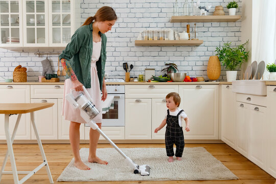 Focused housewife vacuum cleaning floor in kitchen near cute toddler son