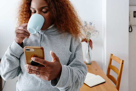 Woman having coffee while checking her phone