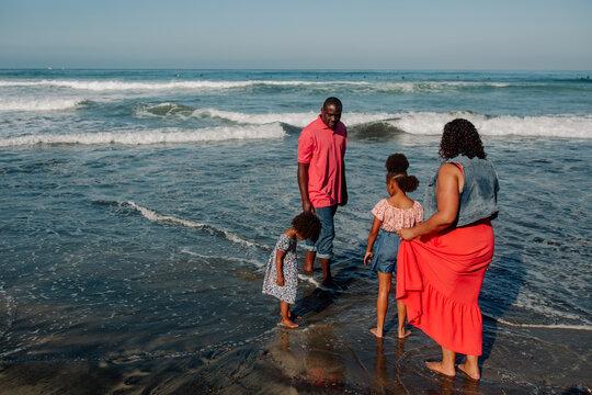 Black family wading in ocean