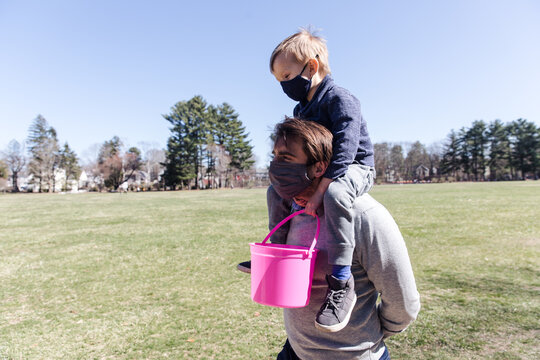 Father carries son on his shoulder while Easter egg hunting