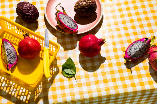 Fruit on checkered tablecloth hard shadows. Tropical foods