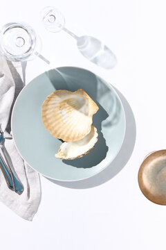 Oyster shell on blue dish. Crystal white tablecloth with glass of water, gray napkin, fork and knife. Minimal seafood cafe table top view. Summer day concept with white table top view.