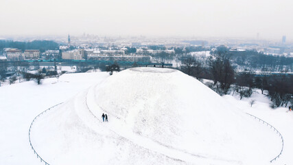 Obraz Panoramic view of the Krakus Mound (Kopiec Krakusa) also called Krak Mound. A tumulus located in the Podgórze district of Kraków, Poland. Tourists can be seen standing. Whole area covered with snow.  - fototapety do salonu
