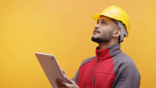 A young Engineer wearing yellow safety helmet holding a tablet in his hand. Studio shot with yellow background. Engineering and construction concept.