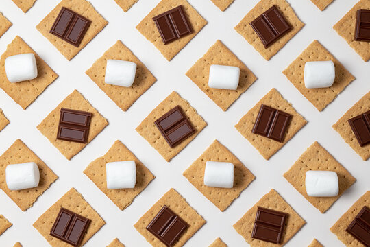 s'mores ingredients. graham cracker squares with  chocolate bars, marshmallows on a white background.
