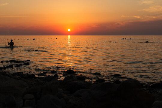 Silhouettes of people swimming in the sea at sunset. Russia, Sea of Azov, Krasnodar Territory, Yeysk.