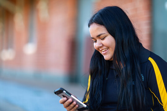 smiling young lady looking at smartphone