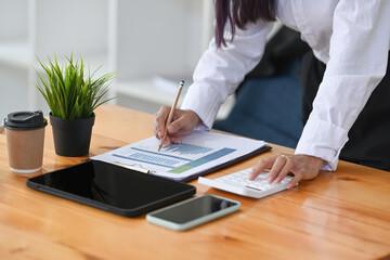 Accountant analysis data charts and using calculator on office desk. - fototapety na wymiar