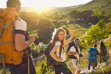 Group of happy backpackers trekking on sunny day. Young tourists traveling and enjoying active summer vacation. Smiling woman looking at camera and waving hand walking down hiking trail with friends