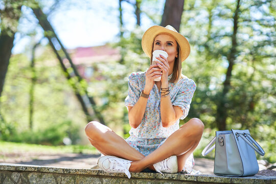 Woman in the hat with a coffee relaxing