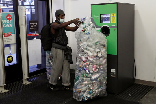A man unloads items for recycling at a redemption station inside a CVS pharmacy near Times Square in New York City