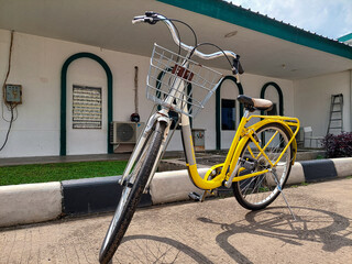 A silver yellow bike with basket