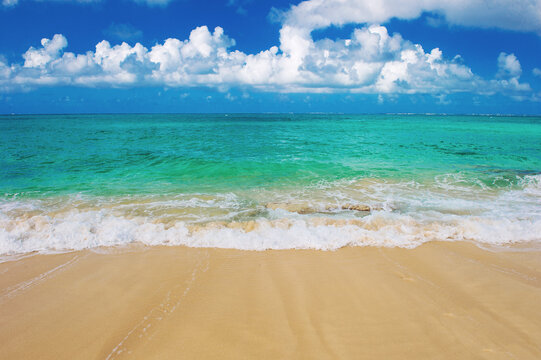 Sand beach turquoise sea blue sky with white clouds